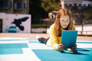 children on the ground on a playground gathered around a tablet reading