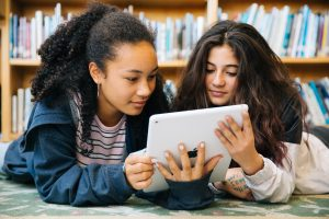 2 girls in library reading from a tablet computer